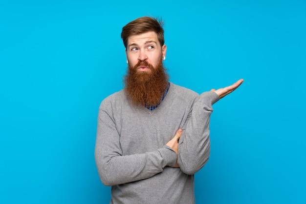 Homem ruivo com barba longa isolado azul infeliz por não entender algo Foto Premium