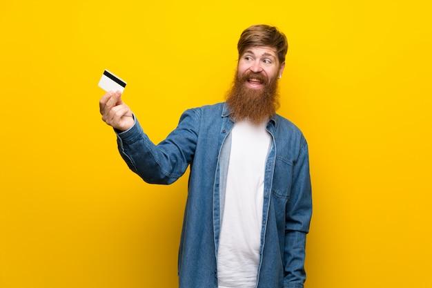Homem ruivo com barba longa isolado parede amarela segurando um cartão de crédito Foto Premium