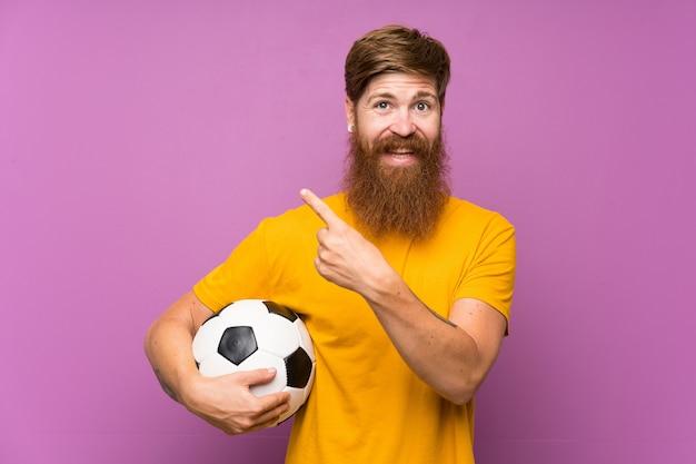 Homem ruivo com barba longa, segurando uma bola de futebol na parede roxa, apontando para o lado para apresentar um produto Foto Premium