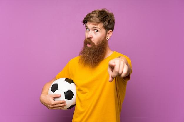 Homem ruivo com barba longa, segurando uma bola de futebol sobre a parede roxa aponta o dedo para você com uma expressão confiante Foto Premium
