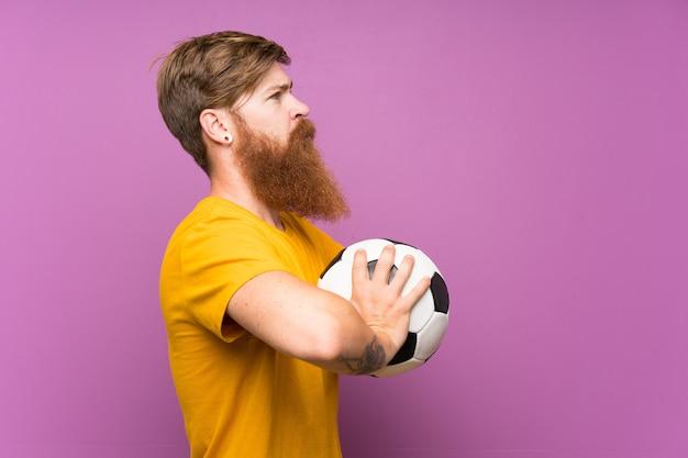 Homem ruivo com barba longa, segurando uma bola de futebol sobre parede roxa isolada Foto Premium