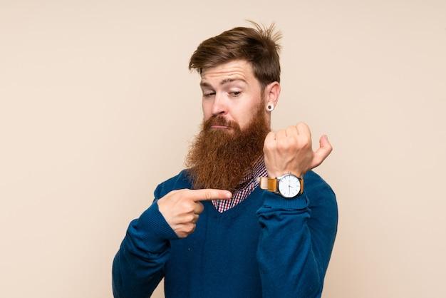 Homem ruivo com barba longa sobre fundo isolado, mostrando o relógio de mão com expressão séria, sério, porque está ficando tarde Foto Premium