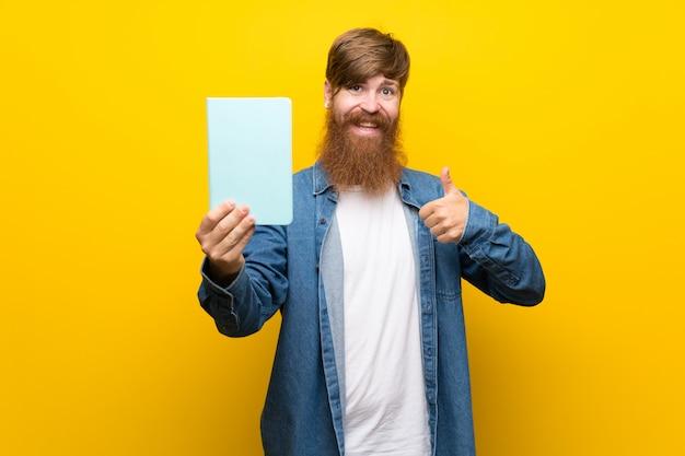 Homem ruivo com barba longa sobre parede amarela isolada, segurando e lendo um livro Foto Premium
