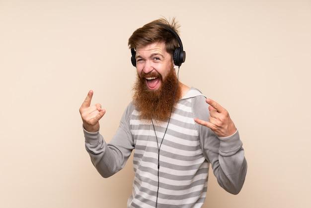 Homem ruivo com barba longa sobre parede isolada, usando o celular com fones de ouvido e dança Foto Premium