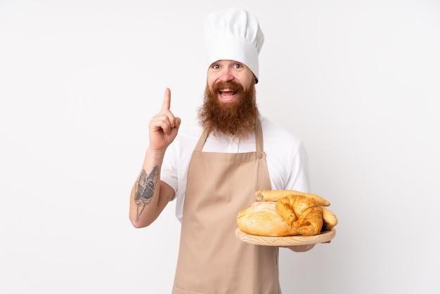 Homem ruivo de uniforme de chef. padeiro masculino segurando uma mesa com vários pães apontando para cima uma ótima idéia Foto Premium