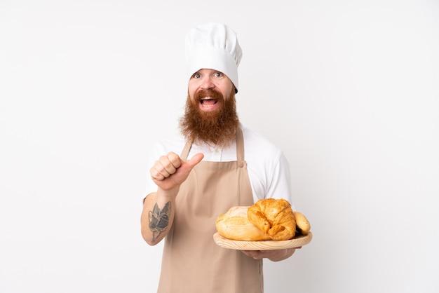Homem ruivo de uniforme de chef. padeiro masculino segurando uma mesa com vários pães apontando para o lado para apresentar um produto Foto Premium