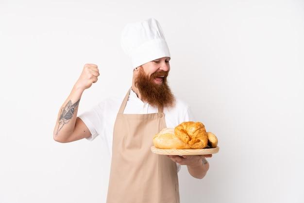 Homem ruivo de uniforme de chef. padeiro masculino segurando uma mesa com vários pães comemorando uma vitória Foto Premium