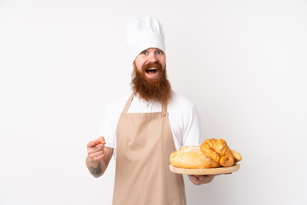 Homem ruivo de uniforme de chef. padeiro masculino segurando uma mesa com vários pães surpreso e apontando o dedo para o lado Foto Premium