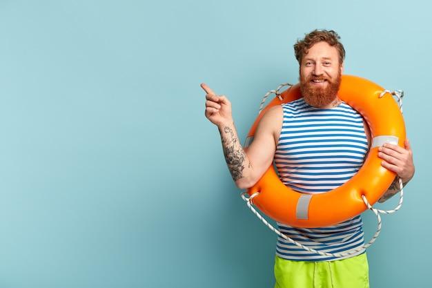 Homem ruivo feliz com cabelo encaracolado, relaxando na praia de verão, posando com uma bóia salva-vidas laranja brilhante Foto gratuita