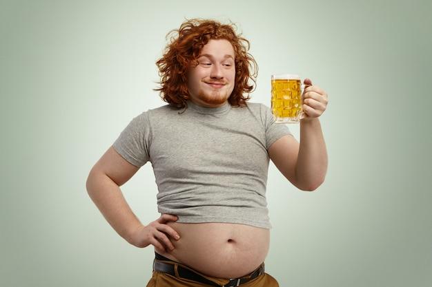Homem ruivo feliz com excesso de peso, com barriga grande, saindo de sua camiseta encolhida, segurando o copo de cerveja gelada, olhando em antecipação, impaciente para sentir seu bom gosto enquanto relaxa em casa depois do trabalho Foto gratuita