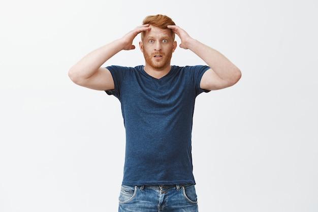 Homem ruivo frustrado e sombrio em uma camiseta azul, segurando a cabeça e olhando com desapontamento, perdendo a aposta, sentindo-se deprimido e arrependido, parado sobre uma parede cinza infeliz Foto gratuita