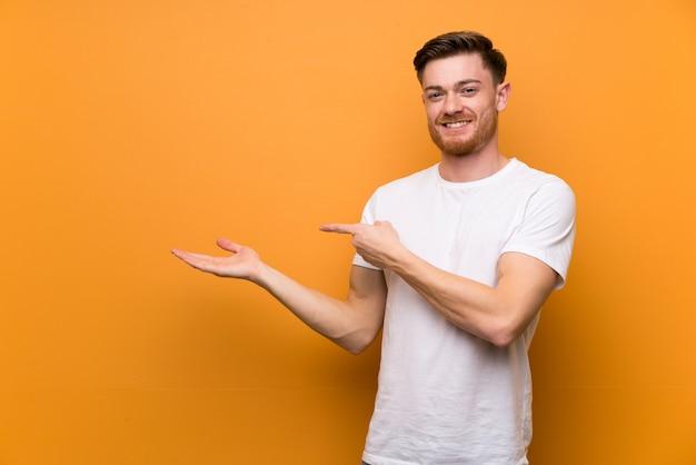 Homem ruivo muro marrom segurando copyspace imaginário na palma da mão para inserir um anúncio Foto Premium