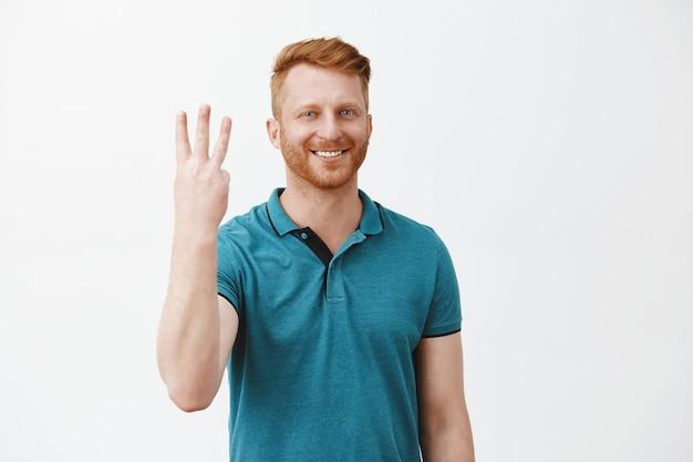 Homem ruivo simpático e bonito, caucasiano, pedindo três doses ao barman, sorrindo amplamente, mostrando o terceiro número e sorrindo amplamente Foto gratuita