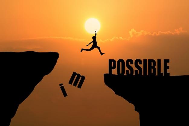 Homem saltando sobre o impossível ou possível sobre o penhasco no fundo do pôr-do-sol, idéia de conceito de negócios Foto gratuita