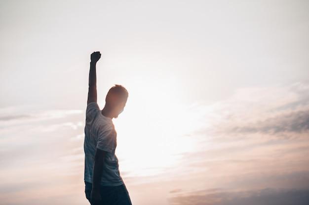 Homem saltitante. jovem louco está pulando no cume rochoso acima da paisagem. silhueta de homem pulando e céu pôr do sol elemento de design. efeito vintage. Foto Premium