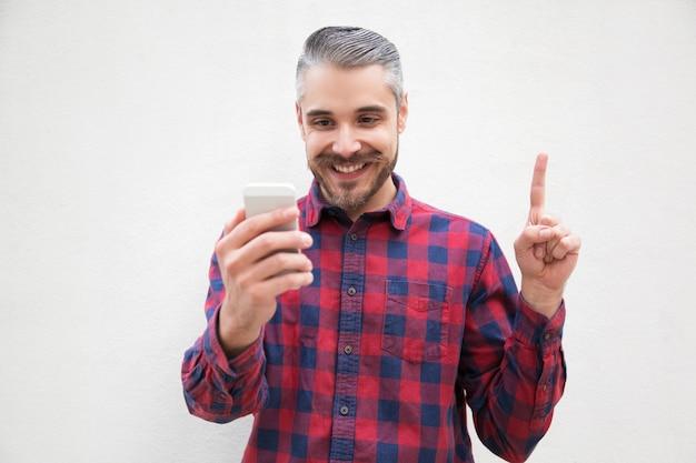 Homem satisfeito com smartphone apontando para cima com o dedo Foto gratuita