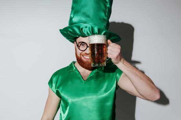 Homem satisfeito em traje de st.patriks segurando cerveja Foto gratuita