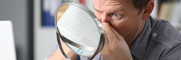 Homem se senta no espelho da frente e pressiona o rosto Foto Premium