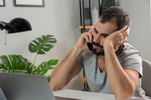 Homem se sentindo cansado enquanto trabalha em casa e fala ao telefone Foto Premium