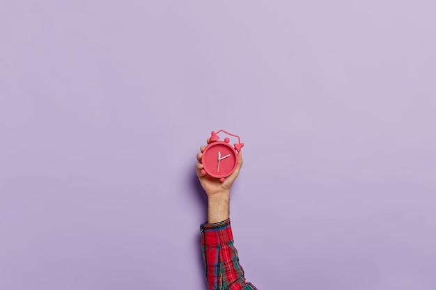 Homem segura pequeno despertador vermelho na mão Foto gratuita
