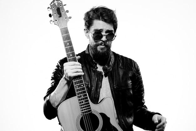 Homem segura uma guitarra nas mãos, vestindo uma jaqueta de couro preta Foto Premium