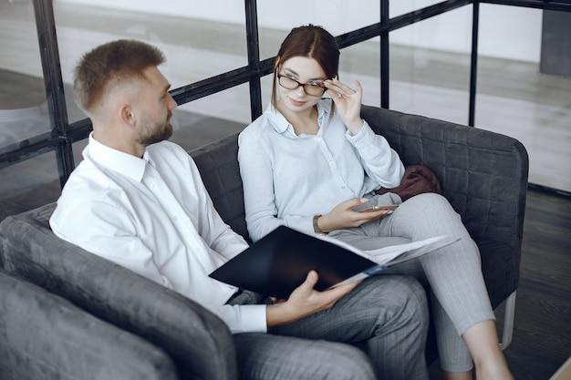 Homem segura uma pasta. parceiros de negócios em uma reunião de negócios. mulher de óculos Foto gratuita