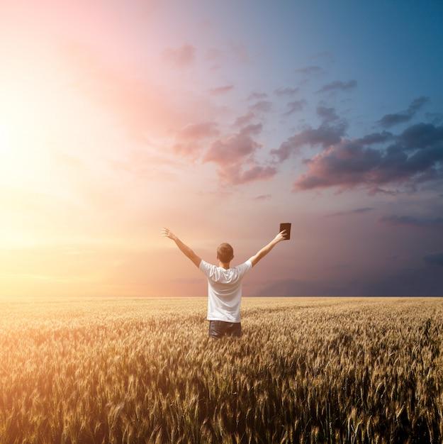 Homem segurando a bíblia em um campo de trigo Foto Premium