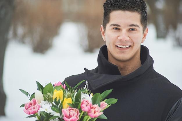 Homem segurando a caixa de presente vermelha com um lindo buquê de florescência tulipas cor de rosa, amarelas e brancas e crisântemos brancos com folhas verdes, ao ar livre Foto Premium
