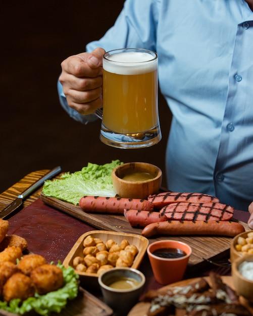 Homem segurando a caneca de cerveja servida com salsichas grelhadas, grão de bico, almôndegas crocantes Foto gratuita