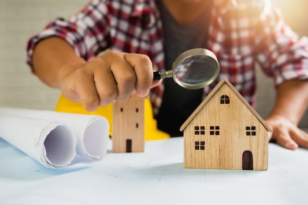 Homem segurando a lupa na casa de brinquedo Foto Premium
