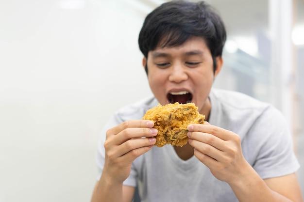 Homem segurando a mão e mostrando farinha de frango frito para comer Foto Premium