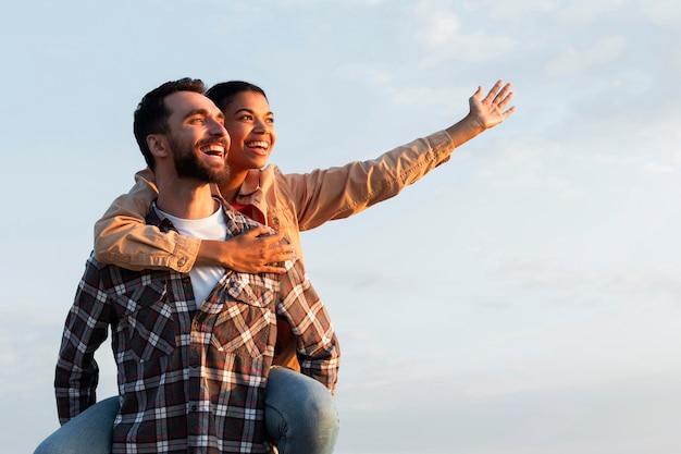 Homem segurando a namorada nas costas com espaço de cópia Foto gratuita