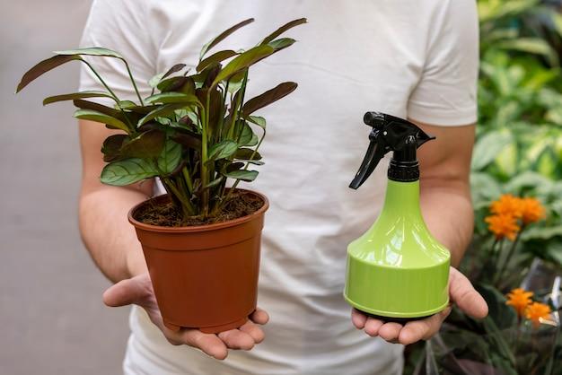 Homem segurando a planta da casa e o frasco de spray Foto gratuita