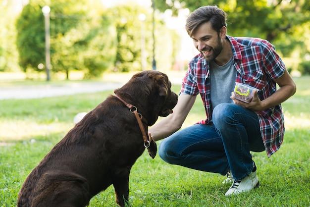 Homem, segurando, alimento, em, recipiente, tocando, com, cão Foto gratuita