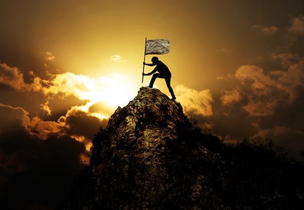 Homem segurando bandeira no pico da montanha e pôr do sol ao ar livre na natureza Foto Premium