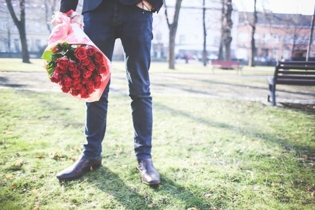 Homem segurando buquê de rosas Foto gratuita