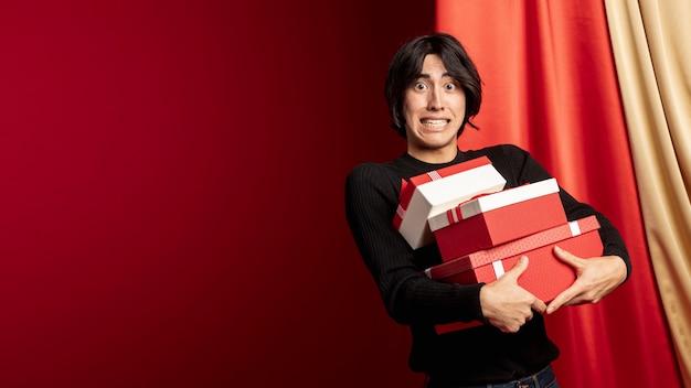Homem segurando caixas para o ano novo chinês Foto gratuita