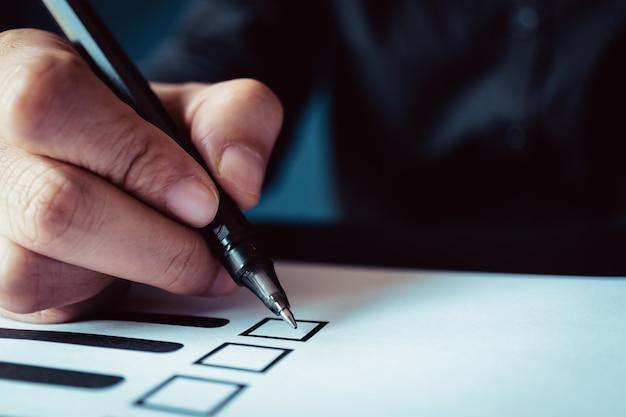 Homem, segurando, caneta, marca, voto, papel, democracia, conceito, retro, tom Foto Premium