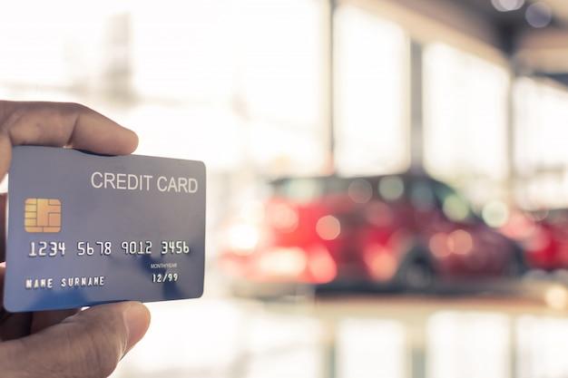 Homem, segurando, cartão crédito, para, obscurecido, bokeh, fundo e-shopping, marketing digital, consumidor, compra, fazendo compras, internet, online, imagem Foto Premium