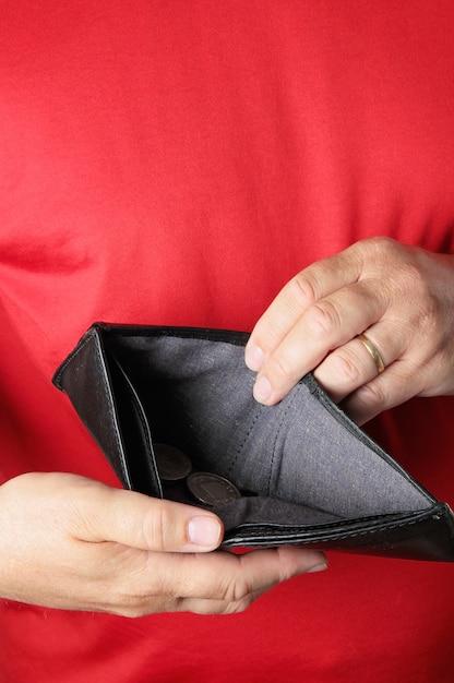 Homem segurando carteira vazia. decepção, ideia de dívidas Foto Premium
