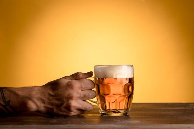 Homem, segurando, copo cerveja, ligado, tabela madeira Foto gratuita