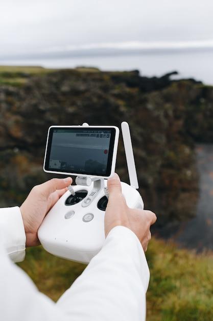 Homem segurando drone e controle remoto na islândia Foto gratuita