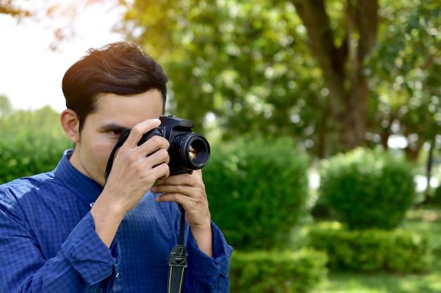 Homem, segurando, e, usando, câmera dslr, e, sentando, sob, árvore, em, parque público, ligado, manhã Foto Premium