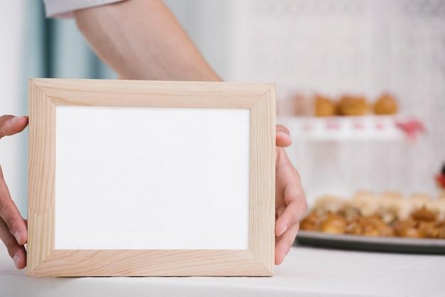 Homem, segurando, frame madeira, com, mock-up Foto gratuita