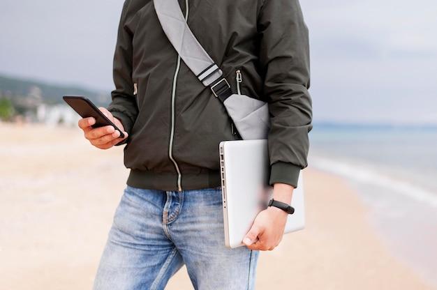 Homem segurando laptop e smartphone na praia Foto gratuita