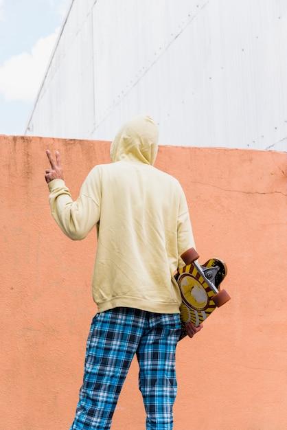 Homem, segurando, longboard, e, mostrando, gesto paz Foto gratuita