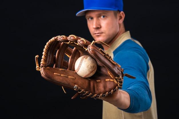 Homem segurando luva e beisebol Foto gratuita