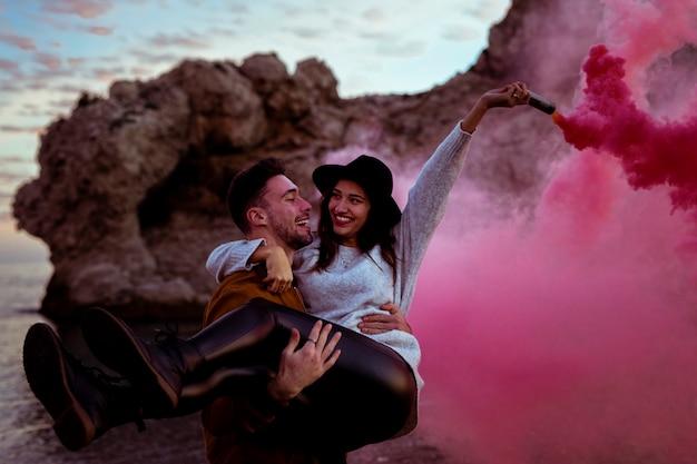 Homem, segurando, mulher, em, braços, com, bomba fumaça Foto gratuita