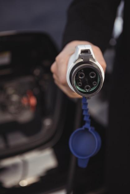 Homem segurando o carregador do carro na estação de carregamento de veículos elétricos Foto gratuita