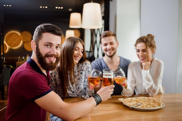 Homem segurando o copo de cerveja e sentado na pizzaria com os amigos. Foto Premium